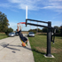 Competitive teenager dunks, side view