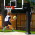 Competitive young child goes in for a layup on a lowered goal